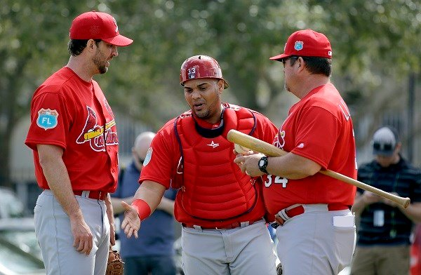 St. Louis Cardinals catcher Brayan Pena, center, talks with pitcher Adam Wainwright, left, and pitching coach Derek Lilliquist during spring training baseball practice Thursday, Feb. 18, 2016, in Jupiter, Fla. (AP Photo/Jeff Roberson)