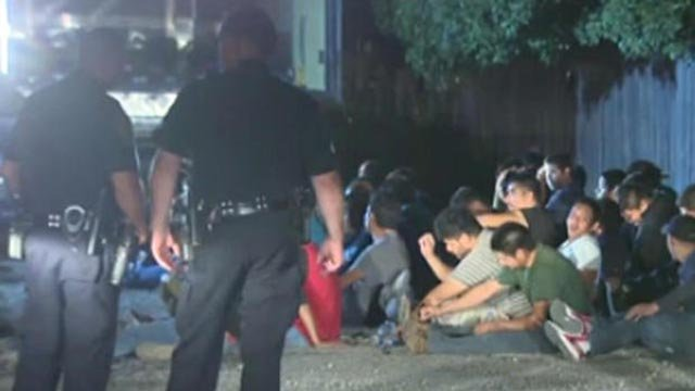 Police officers are seen with some of the 55 people found in back of tractor-trailer stopped in San Antonio on night of June 12, 2018 (Credit: KENS-TV via CBS News)