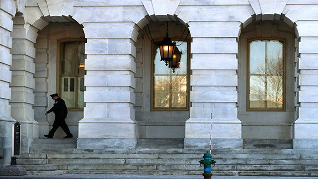 As a bitterly-divided Congress hurtles toward a government shutdown this weekend, a Capitol Police officer walk outside of the Capitol, Friday, Jan. 19, 2018, on Capitol Hill in Washington. (AP Photo/Jacquelyn Martin)